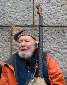 Pete Seeger holding banjo happy hat